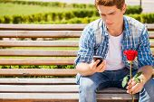stock photo of single man  - Worried young man holding single rose and looking at his mobile phone while sitting on the bench - JPG