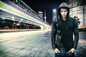 stock photo of hoods  - Gorgeous Young Man in Trendy Hooded Shirt Standing at the City Street While Looking at the Camera - JPG