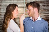 foto of argument  - Casual young couple in an argument against wooden planks - JPG