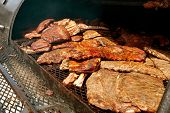 stock photo of slab  - Slabs of barbeque ribs slowly cook inside industrial grill at festival - JPG