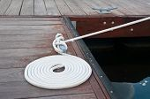 picture of dock  - White rope coiled on a wooden dock and tied to a metal dock cleat - JPG