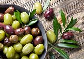stock photo of beside  - Wooden bowl full of olives and olive twigs besides it - JPG