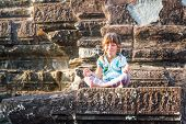 stock photo of krishna  - young happy child girl tourist meditating in angkor wat - JPG