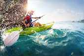 pic of kayak  - Young lady paddling hard the kayak with lots of splashes near the cliff at sunny day - JPG