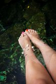 stock photo of cenote  - Fish spa therapy with female legs in mexican cenotes - JPG