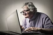 stock photo of ugly  - Elderly man using technology  - JPG
