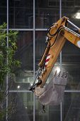 image of hydraulics  - The steel bucket of a hydraulic excavator in front of windows of an office building under construction - JPG