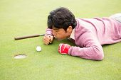 image of cheater  - Golfer trying to flick ball into hole at the golf course - JPG