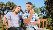 stock photo of argument  - Couple having an argument on park bench on a sunny day - JPG