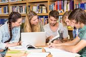 foto of homework  - Group of college students doing homework in the library - JPG