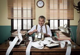 stock photo of 1950s style  - Busy vintage accountant with adding machine surrounded by cash register tape - JPG