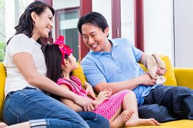 stock photo of stuffed animals  - Chinese Family playing with daughter on sofa holding stuffed animal - JPG