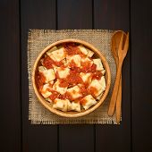 pic of dark side  - Cooked ravioli with homemade tomato sauce in wooden bowl with wooden spoon and fork on the side photographed overhead on dark wood with natural light - JPG