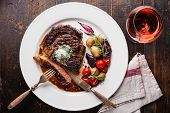 picture of ribeye steak  - Sliced medium rare grilled Beef steak Ribeye with herb butter and baby potatoes and wine on white plate on wooden background - JPG