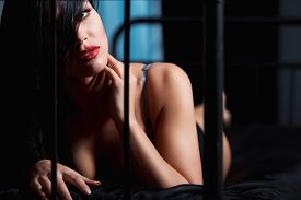 picture of flirt  - Woman with red lips in lingerie flirting on black bed in a very sexual way - JPG