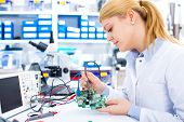 Engineer working with circuits. A woman engineer solders circuits sitting at a table.  Microchip pro poster