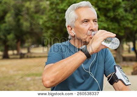 poster of Fit thirsty senior man drinking water before running. Active old man having a break during his jog r