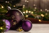 Christmas Toy Purple Ball With A Gold Pattern Next To Small Purple Balls On A Light Table Next To A  poster