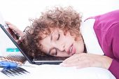 stock photo of boredom  - Tired overworked business woman sleeps on laptop in office - JPG