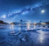 Milky Way Above Frozen Sea Coast, Snow Covered Mountains And Starry Sky With Moon In Winter At Night poster