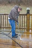 foto of pressure-wash  - Worker pressure washing deck on rear of house - JPG