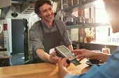 Woman paying by credit card and entering pin code on reader holded by smiling barista in cafeteria.  poster