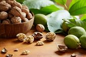 Fresh walnuts with and without shells on a wooden surface. Walnuts, shelled and unshelled. poster