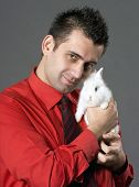 stock photo of peter cottontail  - Handsome young man holding baby rabbit - JPG