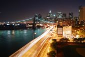 stock photo of new york night  - Urban New York City Manhattan skyline and Brooklyn Bridge with skyscrapers over Hudson River illuminated with lights and busy traffic at dusk after sunset - JPG