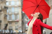 Spontaneous Woman Holding A Red Umbrella Celebrating Success Under The Rain In Winter poster
