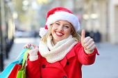 Satisfied Shopper Hoolding Shopping Bags With Thumbs Up On Christmas In The Street poster