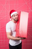 Ready To Unpack Your Gift. Christmas Holiday Celebration. Man Handsome Unshaven Santa Hat Hold Gift  poster