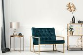 Dark Green Sofa With Golden Frame By A White Wall With Molding In An Elegant Living Room Interior Wi poster