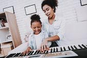 Mother With Daughter Play On Piano. Mother Help Girl With Piano. Positive Emotion. Smile Girl And Sm poster