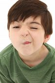 foto of tickle  - Funny seven year old french american boy making sneeze or nose tickle face - JPG