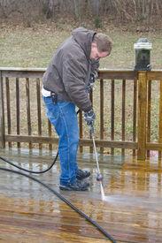 foto of pressure-wash  - Worker pressure washing deck on rear of house - JPG