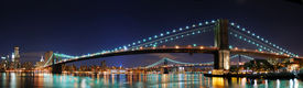 picture of brooklyn bridge  - New York City Manhattan skyline panorama with Brooklyn Bridge and office skyscrapers building in at dusk illuminated with lights at night - JPG