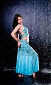 pic of dancing rain  - girl executes east dance in the rain against a dark background - JPG
