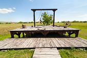 picture of gallows  - Gallows and torture tools on wooden deck outdoor - JPG