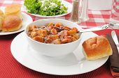 picture of biscuits gravy  - A bowl of beef stew and salad with dinner rolls - JPG