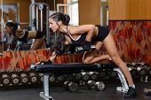 stock photo of bench  - Young sports woman doing exercises with dumbbells in the gym - JPG