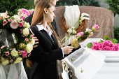 image of coffin  - Mourning man and woman on funeral with pink rose standing at casket or coffin - JPG