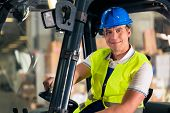 stock photo of vest  - forklift driver in protective vest and forklift at warehouse of freight forwarding company - JPG