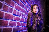 foto of horrifying  - Frightened Pretty Young Woman Against a Brick Wall at Night - JPG