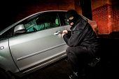 stock photo of hooligan  - Robber and the car thief in a mask opens the door of the car and hijacks the car - JPG