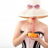 Beautiful pinup girl drinking juice of grapefruit in  sunglssses and panama hat, portrait of young s