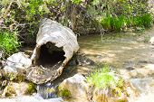 image of hollow log  - A hollow log sits atop a flowing river.