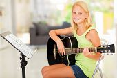 cheerful preteen girl practicing guitar at home