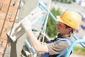 stock photo of putty  - builder worker plastering facade of high - JPG