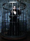 stock photo of caged  - Fashion model in fantasy dress posing in steel cage - JPG